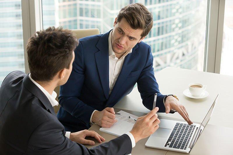 two men sitting at a desk talking